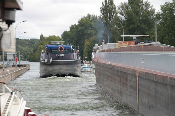 A large barge helps a broken- down cruiser out of the lock