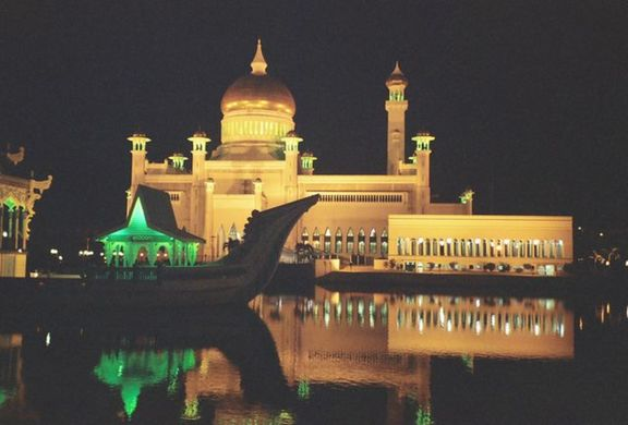 Mosque by night, with sillouhette of ornamental ship in front.